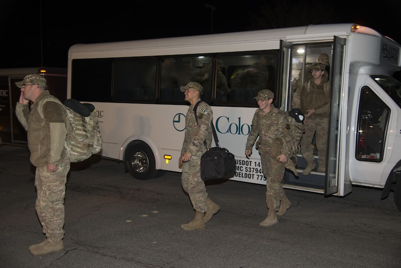 Defenders assigned to the 436th Security Forces Squadron return home from deployment to the Middle East Jan. 21, 2018, at Dover Air Force Base, Del. The 12 Defenders departed the bus after a long day of flights returning them to Dover AFB. (U.S. Air Force Photo by Staff Sgt. Aaron J. Jenne)