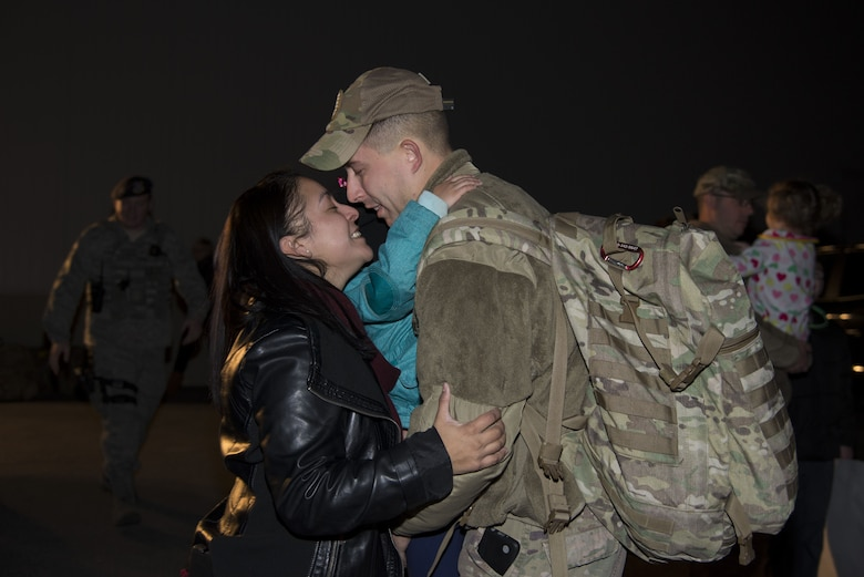 Staff Sgt. Justin Stevenson, 436th Security Forces Squadron defender, kisses his wife, Jamielee, while hugging his daughter, Julia, upon his return home from deployment to the Middle East Jan. 21, 2018, at Dover Air Force Base, Del. Stevenson's team has been deployed since July 2017. (U.S. Air Force Photo by Staff Sgt. Aaron J. Jenne)