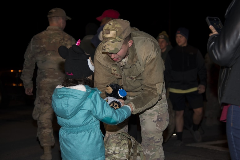 Staff Sgt. Justin Stevenson, 436th Security Forces Squadron defender, hands a stuffed animal to his daughter, Julia, Jan. 21, 2018, at Dover Air Force Base, Del. Stevenson and 11 of his wingmen returned early that morning from a six-month deployment to the Middle East. (U.S. Air Force Photo by Staff Sgt. Aaron J. Jenne)