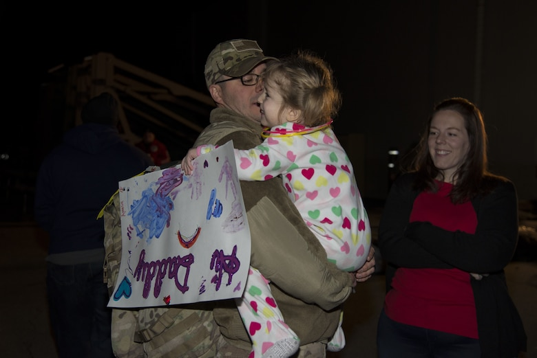 Master Sgt. Michael Johnson, 436th Security Forces Squadron defender, hugs his daughter, Amelia, as his wife, Kelly, looks on Jan. 21, 2018, at Dover Air Force Base, Del. The Johnson family was reunited after a six-month deployment to the Middle East. (U.S. Air Force Photo by Staff Sgt. Aaron J. Jenne)