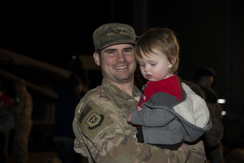 Staff Sgt. Issac McCauley, 436th Security Forces Squadron defender, holds Jaxon, his son, after returning home from deployment Jan. 21, 2018, at Dover Air Force Base, Del. McCauley is one of twelve defenders sent to the Middle East for a six-month deployment. (U.S. Air Force Photo by Staff Sgt. Aaron J. Jenne)