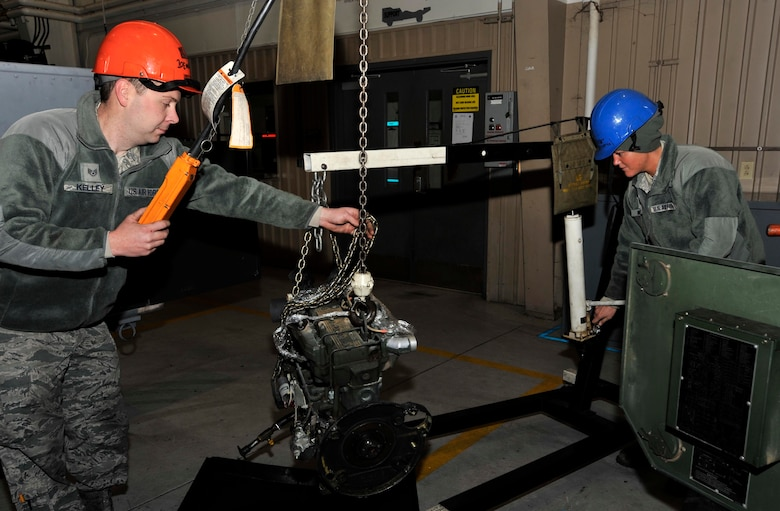U.S. Air Force Staff Sgt. Stephen Kelley, left, and Staff Sgt. Heather Morgan, 20th Equipment Maintenance Squadron aerospace ground equipment craftsmen, remove a generator engine at Shaw Air Force Base, S.C., Jan. 18, 2018.