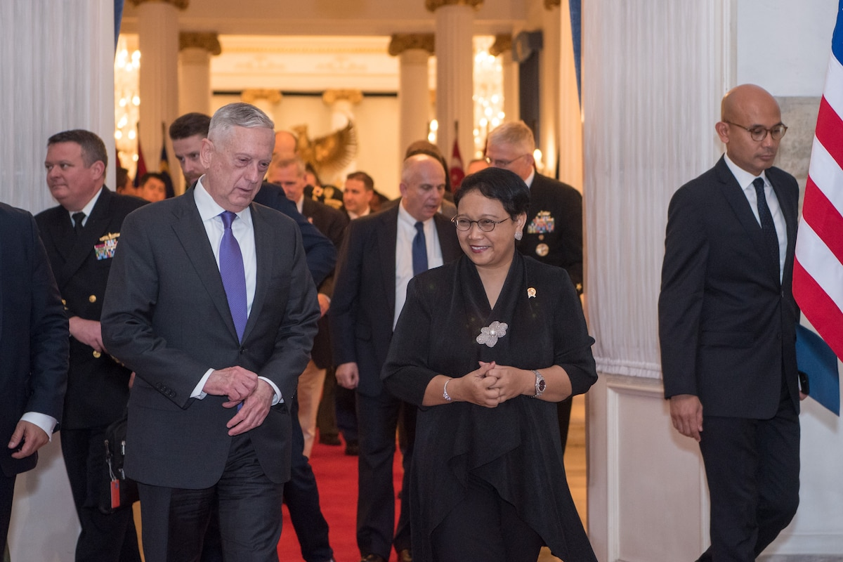 Defense Secretary James N. Mattis walks with Indonesia's foreign minister, followed by a group of people.