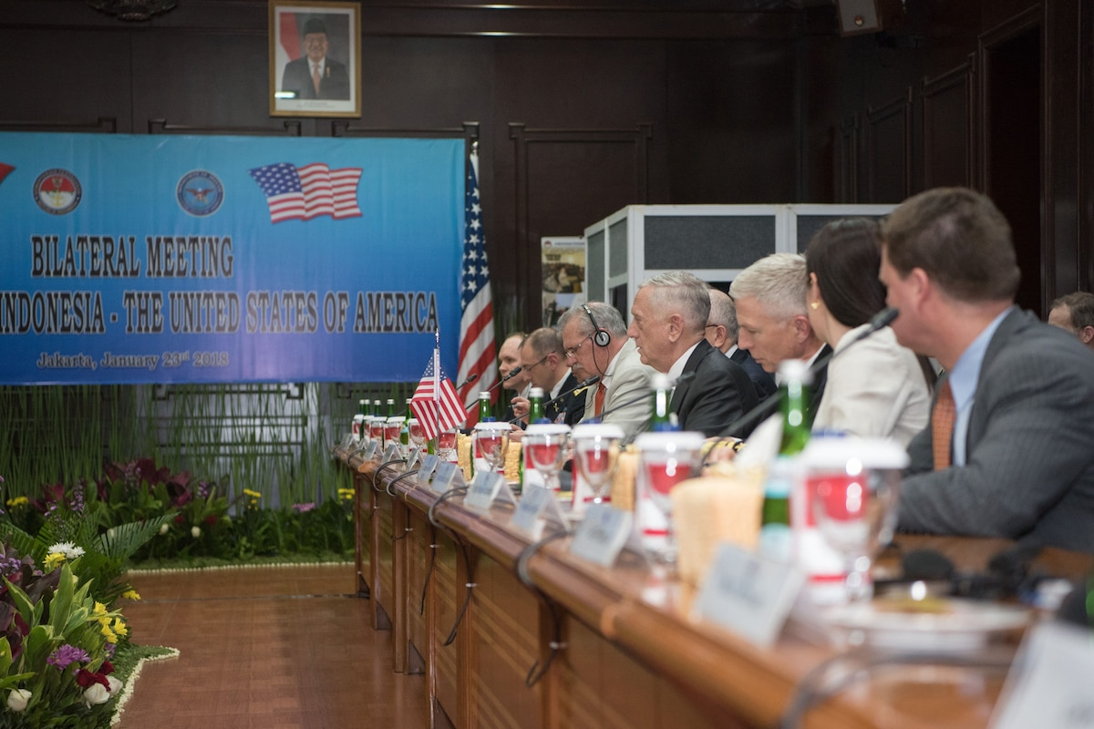 Defense Secretary James N. Mattis sits at a table with a group of people.