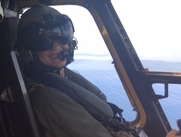A Marine Corps helicopter pilot smiles while flying a CH-53E Super Stallion