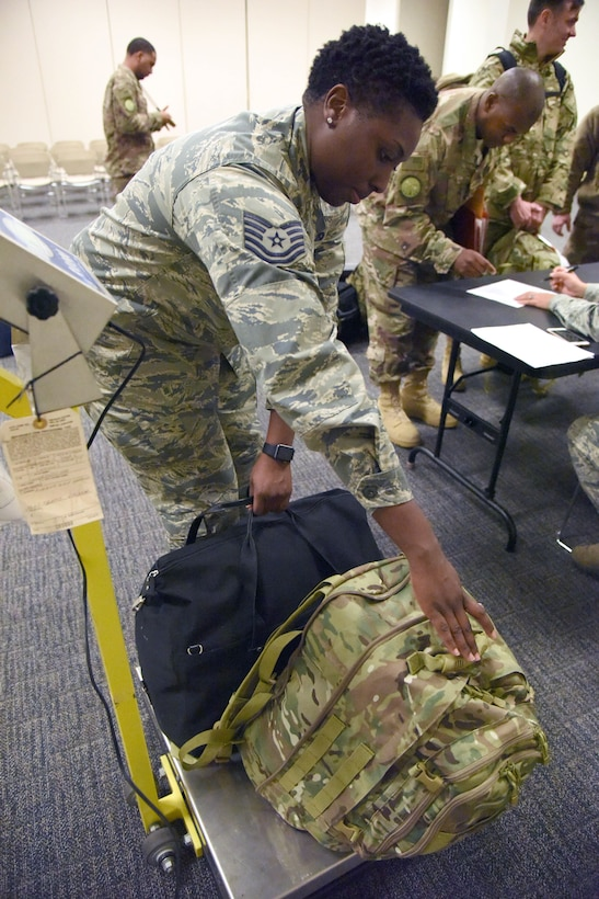 Tech. Sgt. Sabrina Martin, 81st Logistics Readiness Squadron personal property passenger travel NCO in charge, weighs carry-on luggage as Keesler personnel in process for deployment at the Roberts Consolidated Aircraft Maintenance Facility Jan. 8, 2018, on Keesler Air Force Base, Mississippi. Members of the 403rd Wing make preparations for an upcoming deployment to an undisclosed location. (U.S. Air Force photo by Kemberly Groue)