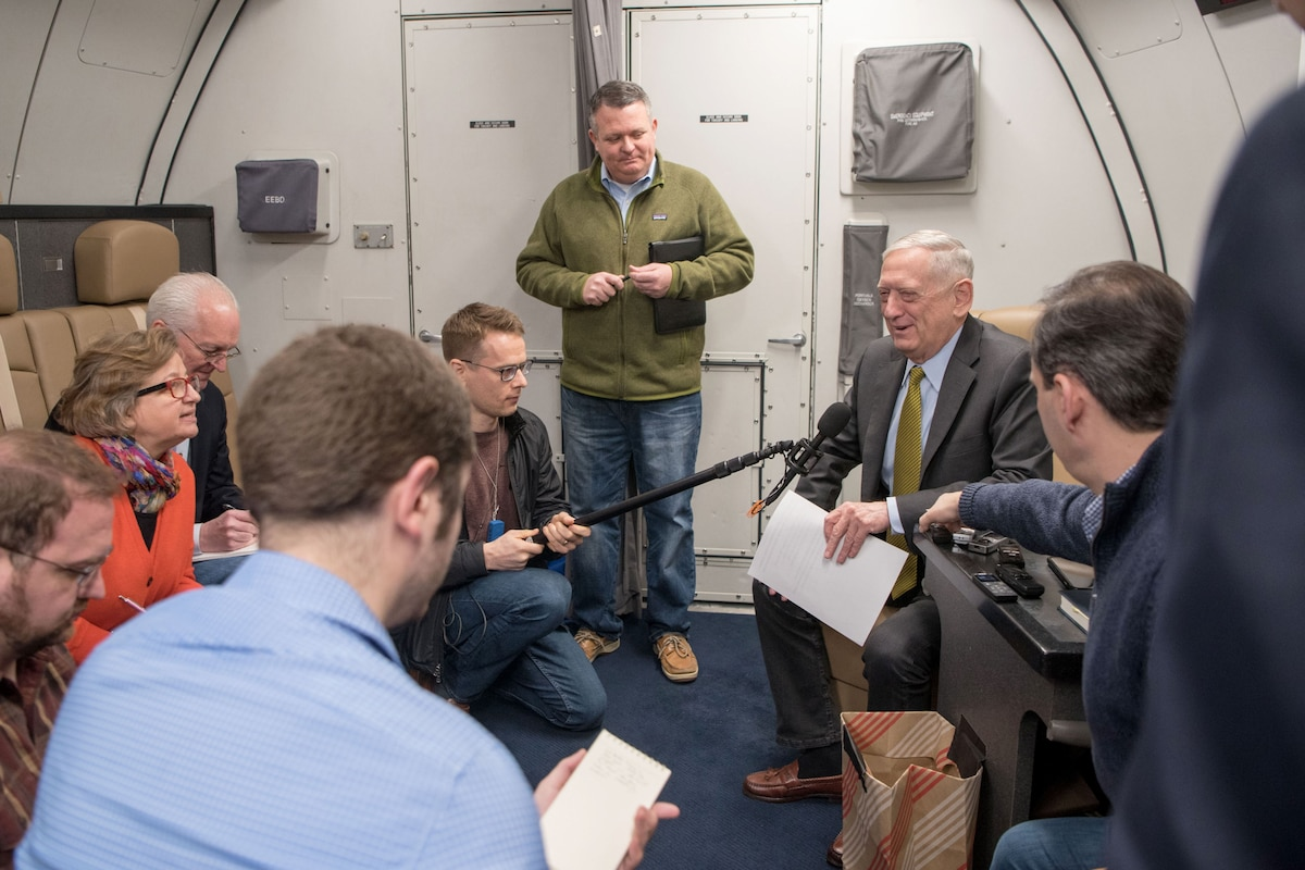 Defense Secretary James N. Mattis sits on a plane speaking to people with recorders.