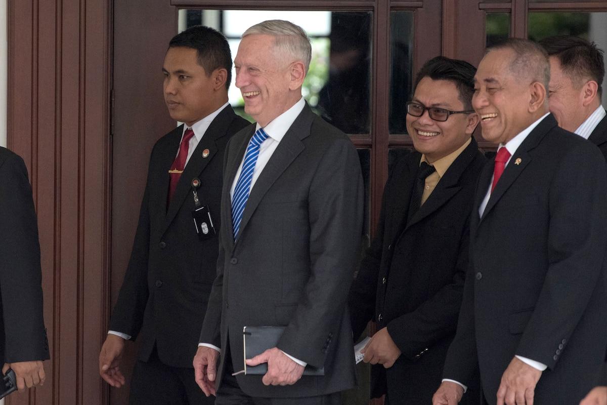 Defense Secretary James N. Mattis walks with a group of people.