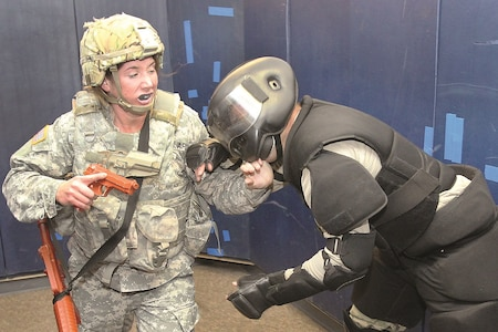 First Lt. Erin Schneider, left, Special Troops Battalion, 1st Infantry Division, assistant operations officer, fends off an attacker as she decides to use her M-9 pistol to control the situation during Level I combatives training at Fort Riley Dec. 15.