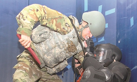 Pfc. Luis Gonzalez, left, 3rd Assault Helicopter Battalion, 1st Aviation Regiment, 1st Combat Aviation Brigade, 1st Infantry Division, intelligence analyst, uses a rubber knife in response to being attacked during Level I combatives training on Fort Riley, Dec. 15.