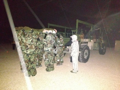 Airmen medics wearing mission oriented protective posture gear load a mannequin on to a transport vehicle during nighttime training at Joint Base San Antonio-Camp Bullis. The training is comprised of scenarios focused on helping Airmen medics understand challenges that might occur during a chemical or biological event.