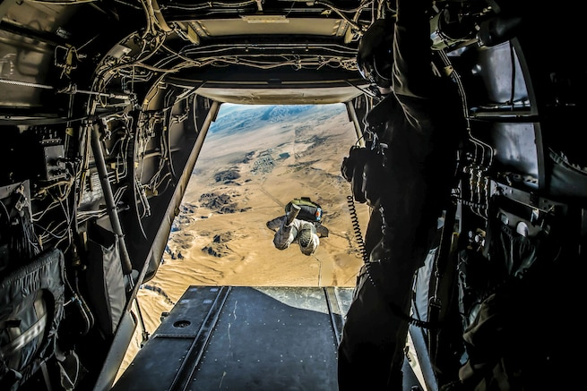 A Marine soars over desert terrain, visible from an opening in the aircraft from which he jumped.