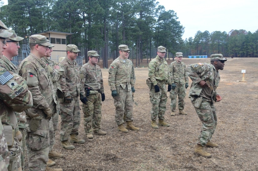Army Staff Sgt. Curtis Graham shows 1st Security Force Assistance Brigade soldiers how to shoot the new XM17 pistol during a demonstration at the Joint Readiness Training Center at Fort Polk, La.