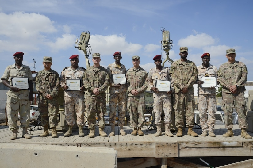 Soldiers assigned to Combined Joint Task Force-Horn of Africa's communications directorate and Djiboutian service members pose for a photo after completing a military-to-military exchange course at Camp Lemonnier, Djibouti.