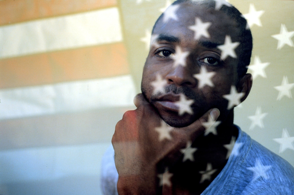 A man poses for a photograph with the reflection of an American flag.