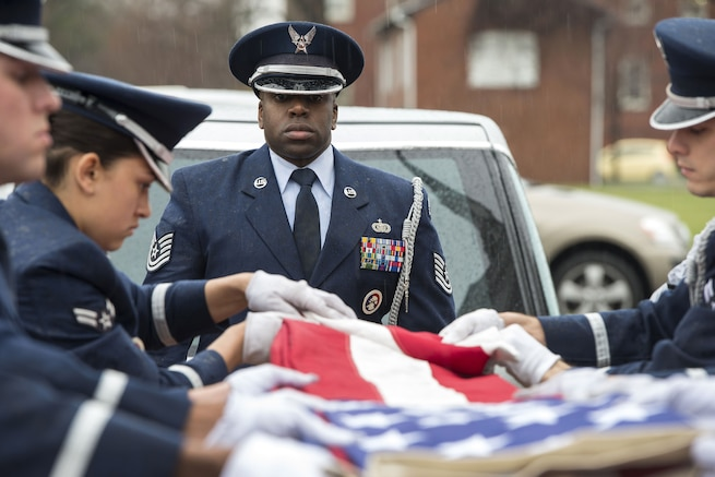 An airman watches the folding of an American flag.