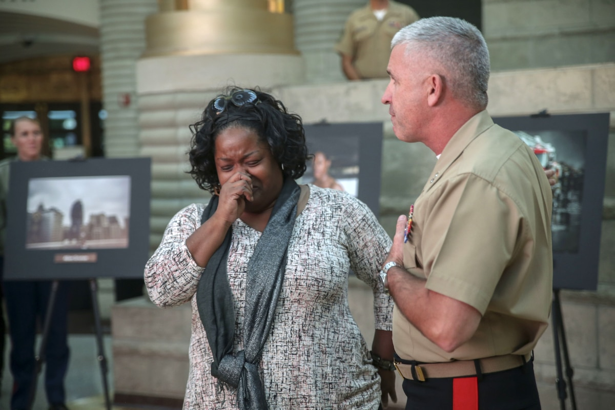 A Marine Corps general talks to a woman who is crying.