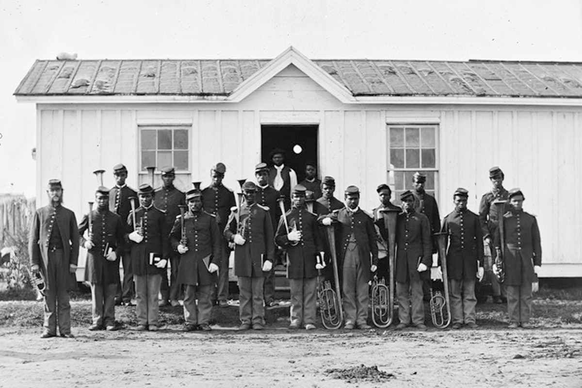 Rows of soldiers pose for a photograph outside of a building.