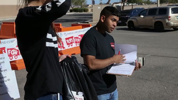 U.S. Marines assigned to Marine Fighter Training Squadron (VMFT) 401 offer helping hands to the Toys for Tots event at the Arizona Western College Conference Center, Dec. 18, 2017. Toys for Tots was founded by U.S. Marine Corps Reservist Maj. William L. Hendricks in 1947 and in 1991, the Secretary of Defense, Dick Cheney, made Toys for Tots an official mission of the Marine Corps Reserves. (U.S. Marine Corps video screenshot by Lance Cpl. Eric Q. Shannon)