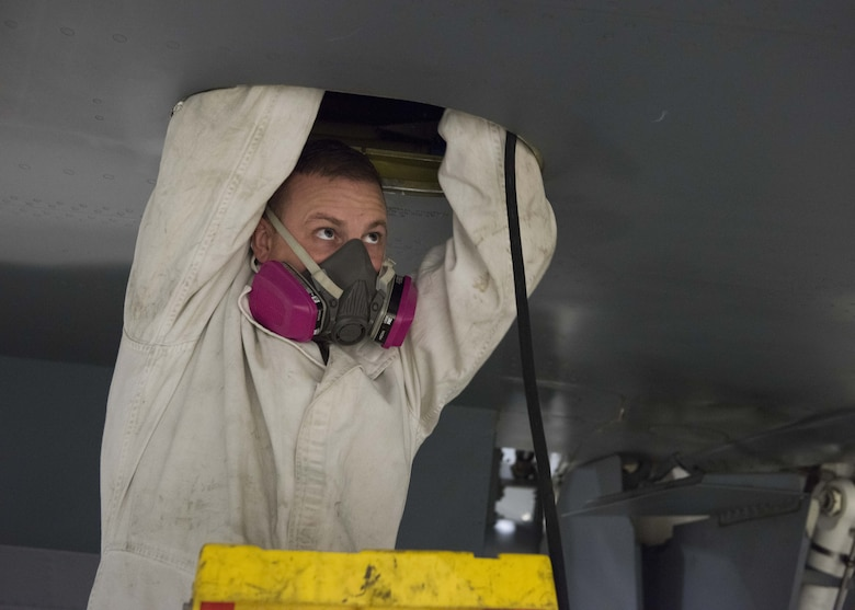 Master Sgt. Zach Kuno, 141st Maintenance Squadron, Aircraft Fuel Systems supervisor, enters a fuel tank on a KC-135 Stratotanker while wearing a respirator and anti-static suit at Fairchild Air Force Base, Washington, Nov. 21, 2017. The atmosphere in and around a fuel tank must be kept at safe levels of no more than 10 percent fuel vapor and oxygen levels between 19.5 and 23.5 percent to minimize health and fire risks. (U.S. Air Force photo/Senior Airman Ryan Lackey)