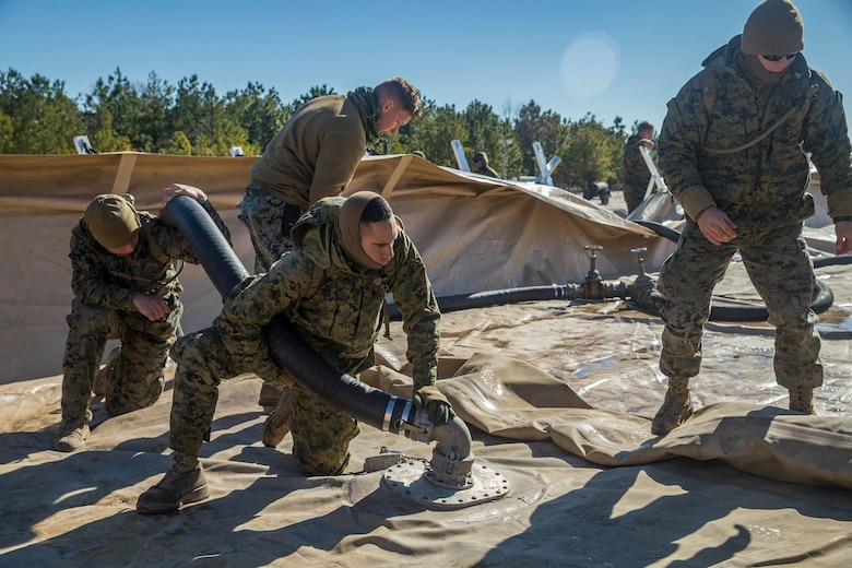 Marines with Bulk Fuel Company, 8th Engineer Support Battalion, 2nd Marine Logistics Group, deconstruct a Tactical Fuel System during a training exercise at Engineer Training Area 2 aboard Camp Lejeune, N.C., Jan. 12, 2018. The exercise was designed to increase proficiency while sustaining ground readiness and combat capability of II Marine Expeditionary Force. (U.S. Marine Corps photo by Lance Cpl. Tyler W. Stewart)