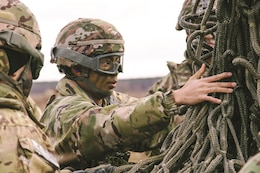 Pvt. Adrianne Castillo, an automated logistical specialist assigned to the 299th Brigade Support Battalion, 2nd Brigade Combat Team, 1st Infantry Division, Fort Riley, prepares equipment to be sling loaded from a helicopter at Skwierzyna, Poland Jan. 4. Sling loading is a method of rapidly transporting equipment that is tethered to the bottom of a helicopter with a rope.