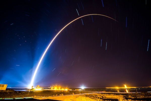 A curving beam of light illuminates a dark blue sky as a rocket launches.