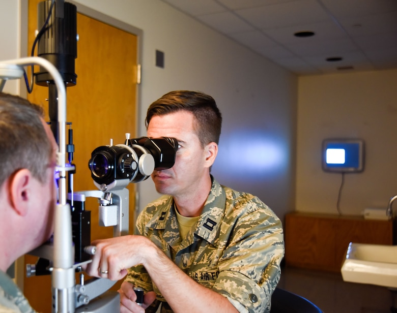 Capt. Brian Gill, 114th Medical Group optometrist, performs an eye exam on a patient at Schofield Health, Wahiawa, Hawaii Clinic, Jan. 17, 2017. Approximately 15 Airmen from the 114th Medical Group worked at Tripler Army Medical Center and Schofield Barracks Health Clinic. (U.S. Air National Guard photo by Staff Sgt. Duane Duimstra)