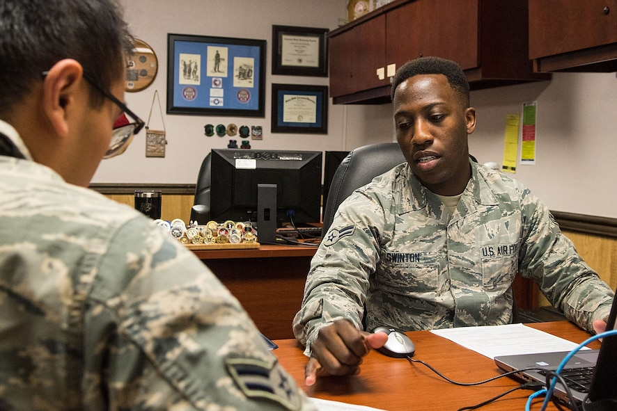 irman 1st Class Vaughn Swinton (right), 4th Comptroller Squadron financial operations technician, assists Airman 1st Class Tin Diep, 4th Aircraft Maintenance Squadron avionics technician, with his in processing, Jan. 17, 2018, at Seymour Johnson Air Force Base, North Carolina.