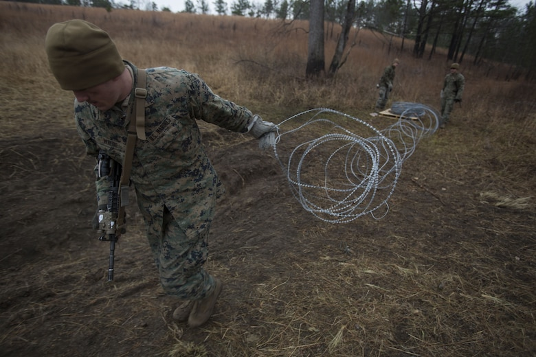 Cpl. Richard Wiebe, a Marine with 2nd Battalion, 8th Marine Regiment, drags a section of concertina wire to create an obstacle at a platoon live-fire range during a pre-deployment training exercise at Fort A.P. Hill, Va., Dec. 7, 2017. The Marines are conducting the training to maintain proficiency at the squad, platoon, company, and battalion-level of warfighting in preparation for an upcoming deployment to Japan. The Marines patrolled, detonated Bangalore torpedoes to breach obstacles, threw M67 fragmentation grenades to clear trenches, and conducted live-fire movements to take an objective. (U.S. Marine Corps photo by Lance Cpl. Ashley McLaughlin)