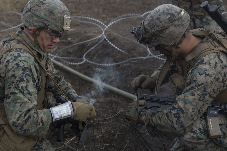 Marines with 2nd Battalion, 8th Marine Regiment activate the blasting caps for a Bangalore torpedo at a platoon live-fire range during a deployment for training exercise at Fort A.P. Hill, Va., Dec. 7, 2017. The Marines are conducting the training to maintain proficiency at the squad, platoon, company, and battalion-level of warfighting in preparation for an upcoming deployment to Japan. The Marines patrolled, detonated Bangalore torpedoes to breach obstacles, threw M67 fragmentation grenades to clear trenches, and conducted live-fire movements to take an objective. (U.S. Marine Corps photo by Lance Cpl. Ashley McLaughlin)