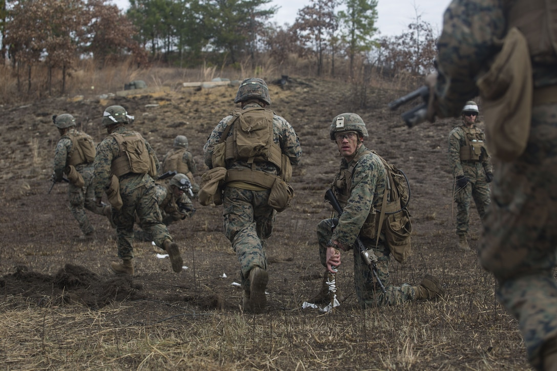 Cpl. Richard Wiebe, a combat engineer with 2nd Battalion, 8th Marine Regiment, guides Marines through a cleared obstacle at a platoon live-fire range during a deployment for training exercise at Fort A.P. Hill, Va., Dec. 7, 2017. The Marines are conducting the training to maintain proficiency at the squad, platoon, company, and battalion-level of warfighting in preparation for an upcoming deployment to Japan. The Marines patrolled, detonated Bangalore torpedoes to breach obstacles, threw M67 fragmentation grenades to clear trenches, and conducted live-fire movements to take an objective. (U.S. Marine Corps photo by Lance Cpl. Ashley McLaughlin)