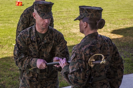 Sgt. Maj. David A. Wilson, off-going sergeant major for I Marine Expeditionary Force Information Group, passes the non-commissioned officer's sword to Col. Dawn R. Alonso, commanding officer, I MIG, during a relief and appointment ceremony at the 11 area parade deck aboard Camp Pendleton, California, Jan. 18, 2018.