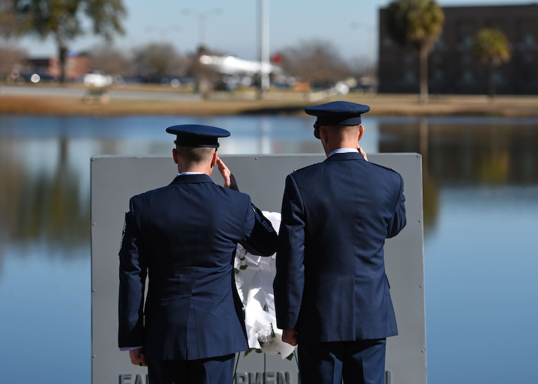 U.S. Air Force Chief Master Sgt. Daniel Hoglund, 20th Fighter Wing (FW) command chief, left, and Col. Daniel Lasica, 20th FW commander, render honors after placing a wreath during a Prisoner of War Medal presentation ceremony at Shaw Air Force Base, S.C., Jan. 19, 2018.