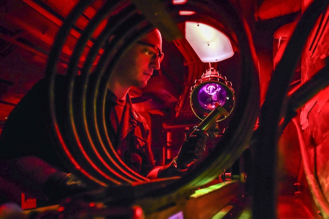 A sailor, illuminated in red and framed by a spiral structure, uses a light to look at an aircraft part he's holding.
