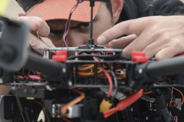 Jason Cassulis, a member of the 2016 Air Force Research Laboratory Commanders Challenge opposition force, sets up and checks a DJI S1000 drone during the setup day at the Nevada National Security Site, Las Vegas, NV., Dec. 9, 2016. This year teams were given the challenge of solving issues revolving around drones, and are demonstrating their solutions to judges. (U.S. Air Force photo by Wesley Farnsworth)