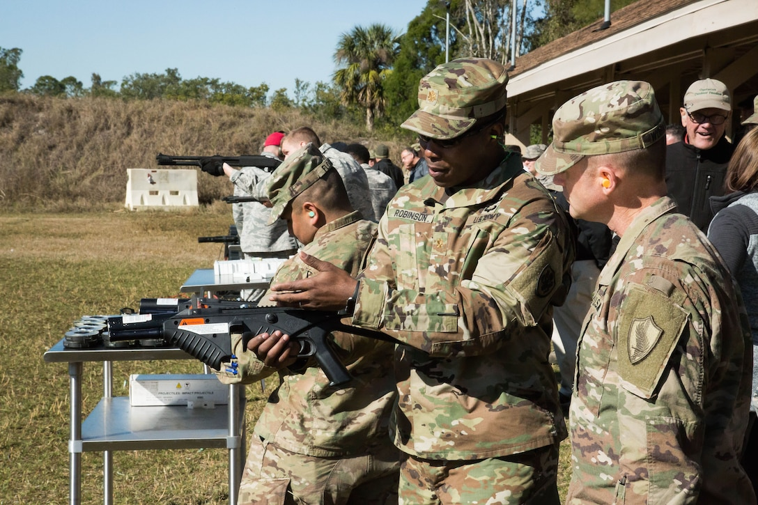 U.S. Army MAJ Kendall Robinson, Division Chief, Capabilities and Requirements, Joint Non-Lethal Weapons Directorate shows a Soldier an FN303 compressed air launcher. Joint service military personnel from U.S. Central Command (USCENTCOM) and supporting commands had the opportunity to fire non-lethal weapons (NLW) at the MacDill Air Force Base firing range during a familiarization event (FAMFIRE), Jan. 18, 2018. The FAMFIRE was a demonstration of NLW capabilities, and a show of how NLW may be used in conjunction with lethal weapon systems to enhance effectiveness and efficiency in military operations. (Photo by Tom Gagnier)