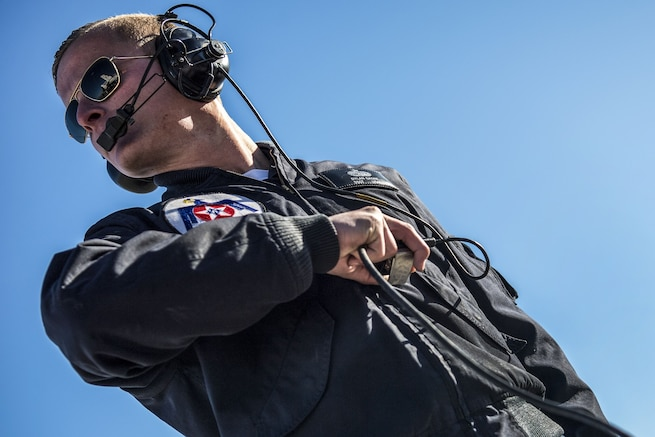 An airman, shown at a titled angle, wears headphones and holds their wires in one hand.