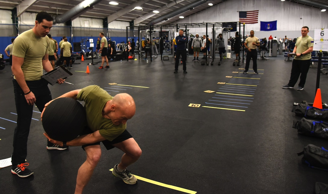 Senior Master Sgt. Kenneth Blakeney (second from left), 9th Air Support Operations Squadron, Fort Hood, Texas, launches a medicine ball at the fitness center at Joint Base Andrews, Md., Jan. 9, 2018. (U.S. Air Force photo by Staff Sgt. Joe Yanik)