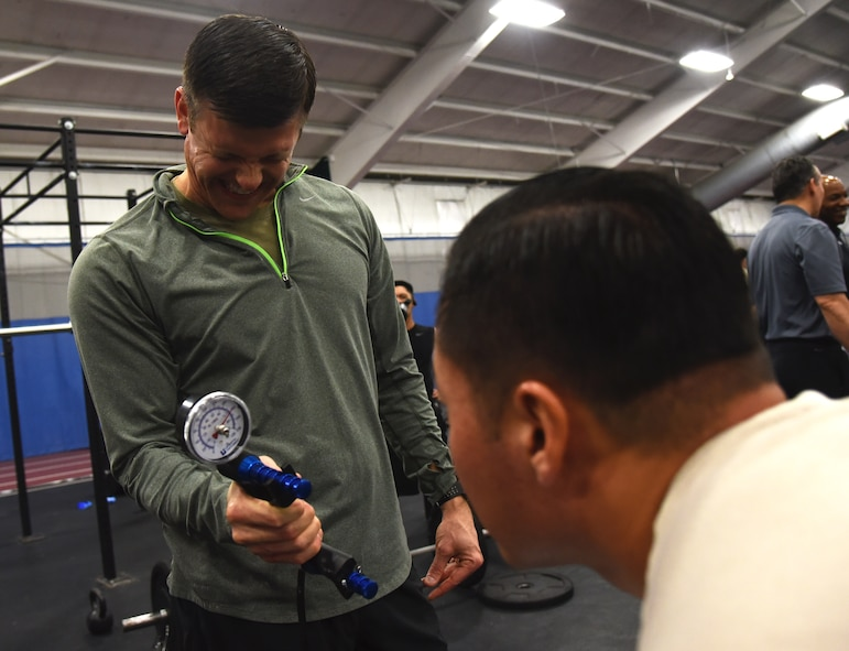 Master Sgt. Paul Foles (left), 17th Special Tactics Squadron, squeezes a dynamometer that measures grip strength during an occupational fitness demonstration performed by members of the Air Force's special  operations community at Joint Base Andrews, Md., Jan. 9, 2018. (U.S. Air Force photo by Staff Sgt. Joe Yanik)