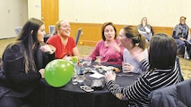 Participants laugh as they discuss the possible answer to a question during the first Trivia Night Jan. 13 at Riley's Conference Center. The trivia questions spanned from the years 2000 to 2017 and focused on topics like movies and celebrities with sprinkling of news and historical events in between. The trivia champions received a gift basket of 2000s-themed goods.