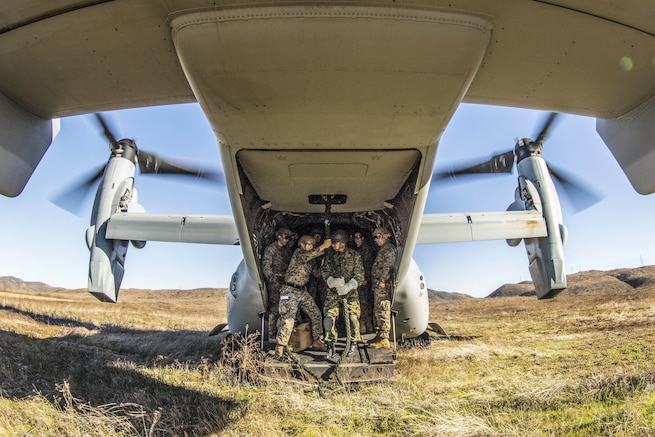 A group of Marines crowds around a rope in the back of an aircraft parked in a field.
