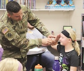 Staff Sgt. Timothy Muckle, chaplain assistant 1st Infantry Division Sustainment Brigade, teaches students how to render a proper hand salute during the adopt-a-school visit at Mission Valley Unified School District 330 in Eskridge, Kansas, Tuesday Nov. 28. The hand salute is one of the most common courtesies in the Army and the students wanted to learn how to properly render it.