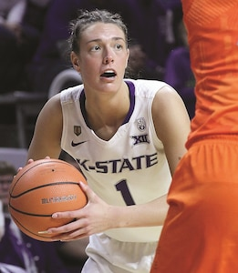 Kansas State University's Kaylee Page looks to make a pass during a victory over the Oklahoma State Cowgirls at Bramlage Coliseum Jan. 13. The K-State women's team hosted a military appreciation day for families of the 1st Infantry Division and Fort Riley. The KSU women's basketball team wears the patch of the 1st Infantry Division Sustainment Brigade on their uniforms as part of a partnership program between KSU and the 1st. Inf. Div.