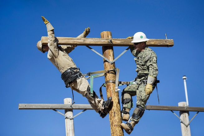A sailor leans back atop a utility pole as another stands on the other side of the pole.