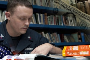 A service member reads a book in a library..