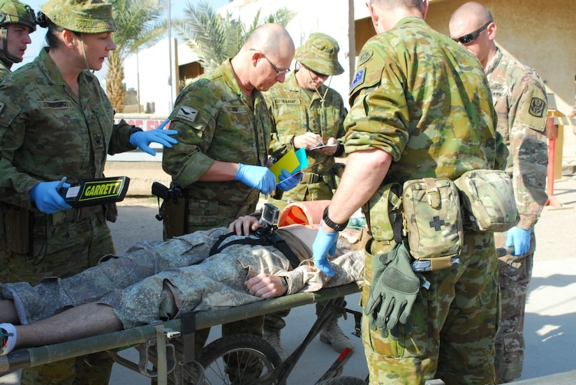 Soldiers assigned to the 449th Combat Aviation Brigade and medical personnel assigned to the Australian army work together to assess a patient's initial injuries after a simulated gas bottle explosion during a mass casualty training exercise at Camp Taji, Iraq, Jan. 18, 2018. This training is part of the overall Combined Joint Task Force Operation Inherent Resolve building partner capacity mission which focuses on training and improving the capability of partnered forces fighting the Islamic State of Iraq and Syria. Army photo by Staff Sgt. Leticia Samuels
