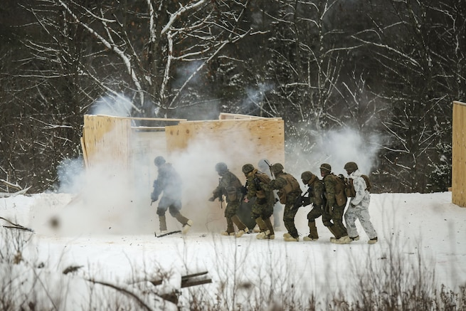 Marines breach and clear a building in a cold, mountainous environment.