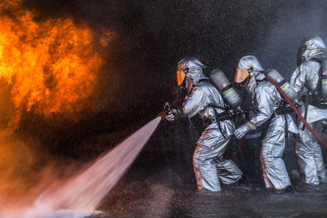 Marines wearing silver protective gear use a hose to spray water on flames.