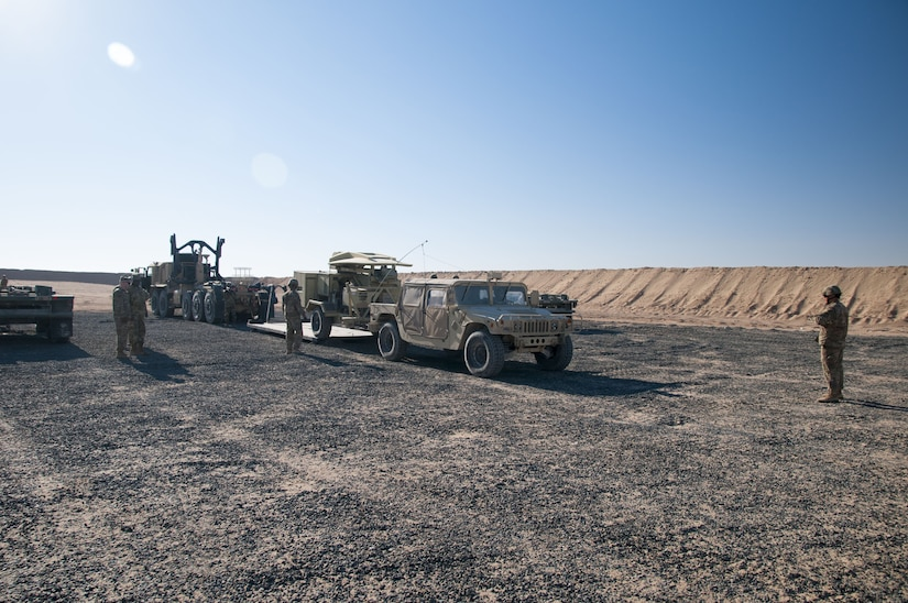 1072nd Transportation Company Soldiers work with 115th Signal Battalion Soldiers to rapidly unload a generator, a satellite transportable terminal, and two humvees during an emergency deployment readiness exercise, or EDRE, Jan. 12, 2018, on Udairi Range Complex near Camp Buehring, Kuwait.